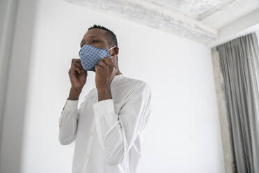Man putting on reusable face mask indoors - AHSF02761