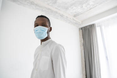 Portrait of man wearing disposable face mask indoors - AHSF02764