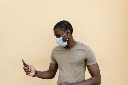 Man wearing mask while using smart phone against beige colored wall - EGAF00180