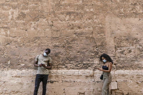 Man and woman wearing masks while using smart phones against weathered wall - EGAF00192