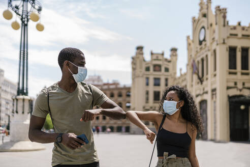 Man and woman wearing masks while greeting each other with elbows in city - EGAF00201