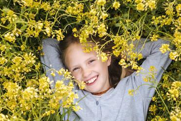smiling girl lying in rape flowers - EYAF01126