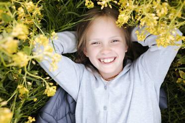 Smiling girl lying in rape flowers - EYAF01129