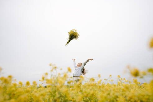 Smiling girl throwing bouquet of rape flowers up - EYAF01132