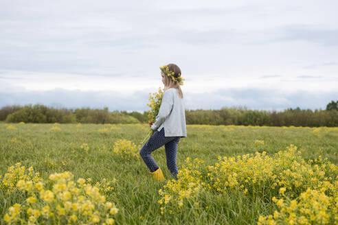 Girl walking with bouquet of rape flowers on rape field - EYAF01138