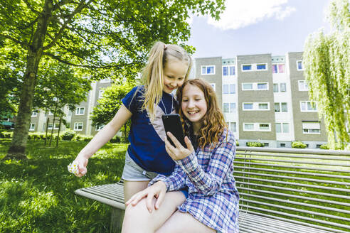 Smiling sisters sharing smart phone on bench in park - IHF00350