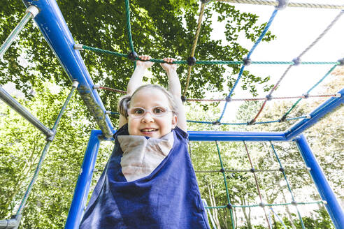 Smiling cute girl hanging from jungle gym at playground in park - IHF00353
