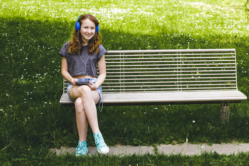Smiling girl listening music through headphones while sitting on bench at park - IHF00356
