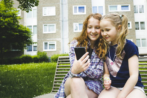 Smiling siblings sharing smart phone while sitting on bench at park - IHF00359
