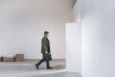 Businessman with briefcase leaving sparse room - MEUF00867