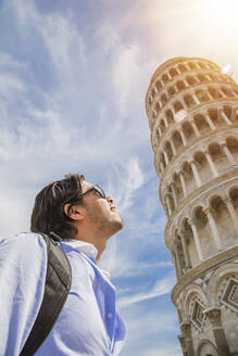 Male tourist looking at Leaning Tower of Pisa against sky, Pisa, Tuscany, Italy - FLMF00230