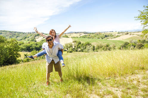 Happy mid-adult couple enjoying countryside on sunny day - FLMF00233