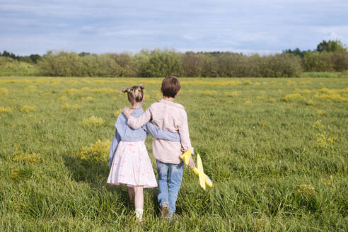 Boy holding toy airplane while standing with arm around sister on rape field - EYAF01146