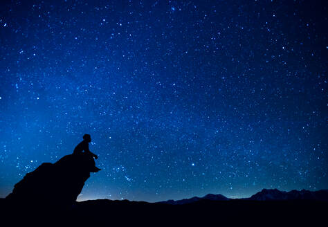 Silhouette Man Sitting On Rock Against Constellation In Blue Sky - EYF05800