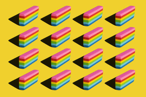 Pattern of rainbow colored erasers against yellow background - XLGF00203