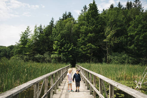 Brother and sister holding hands while standing on wooden footbridge over marsh - JVSF00009