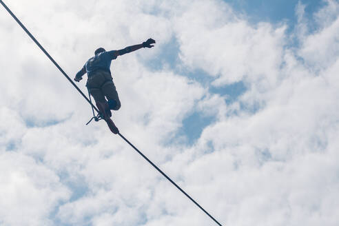 Low Angle View Of Man With Arms Outstretched Walking On Tightrope Against Cloudy Sky - EYF05964