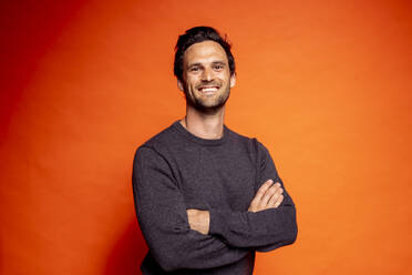 Smiling handsome man standing with arms crossed against orange background - DAWF01597