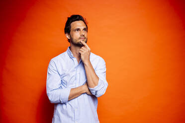Thoughtful handsome man looking away while touching chin against orange background - DAWF01603
