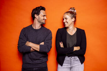 Happy mid adult couple looking at each other while standing with arms crossed against orange background - DAWF01612
