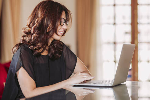 Smiling businesswoman using laptop while sitting at table in living room - LJF01583