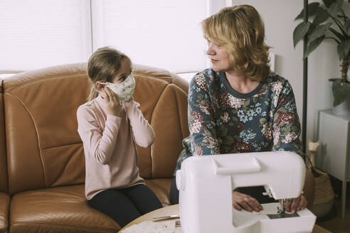 Mature woman looking at granddaughter wearing homemade face mask - VBF00094