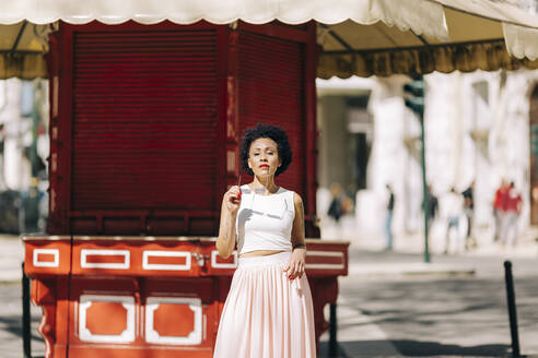 Stylish woman holding sunglasses while standing in city during sunny day - DCRF00324