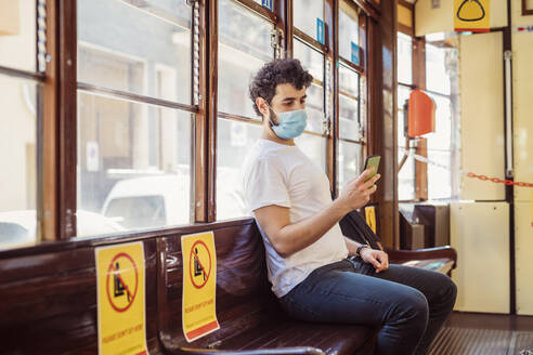 Young man wearing face mask using smart phone while sitting in tram - MEUF00923