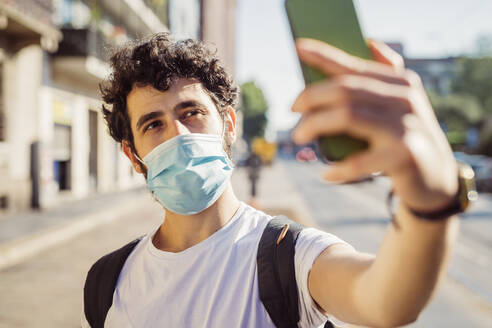 Close-up of man wearing face mask taking selfie with smart phone in city - MEUF00932