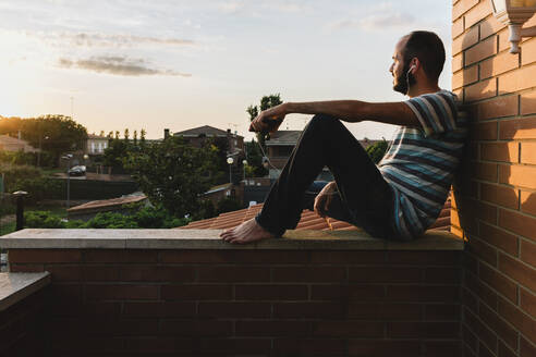 Thoughtful man listening music while sitting on retaining wall against sky during sunset - XLGF00210