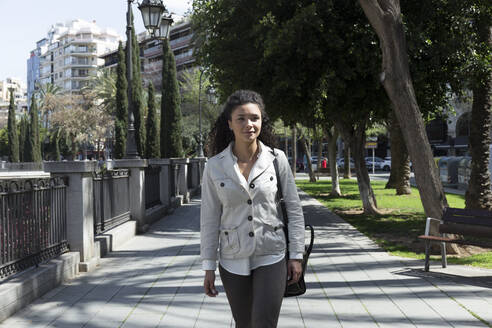 Stylish businesswoman looking away while walking on footpath in park - JPTF00558