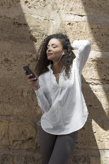 Stylish businesswoman with curly hair using smart phone while standing against wall - JPTF00564
