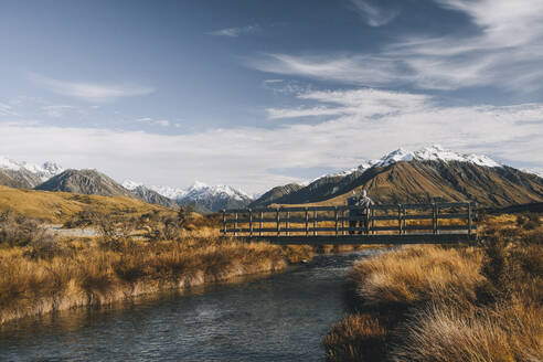 A couple stands in a bridge over a creek Lake Clearwater, Southern Alp - CAVF85402