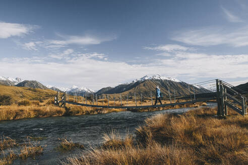 A young woman hikes towards the summit of Mt Sunday, Southern Alps, NZ - CAVF85405