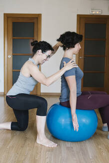 Female physiotherapist assisting patient sitting on fitness ball in health club - XLGF00212