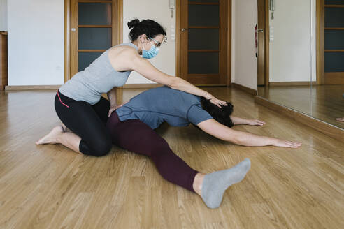 Physiotherapist wearing mask stretching patient's body on floor in health club - XLGF00218
