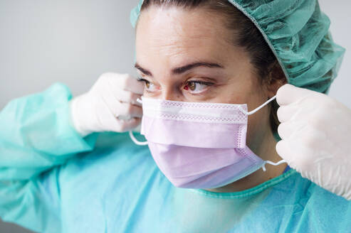Close-up of nurse wearing surgical mask looking away in clinic - JCMF00874