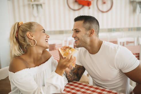 Happy young couple eating pizza while sitting in restaurant - MIMFF00054