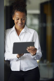 Portrait of smiling businesswoman using digital tablet in office - RBF07719