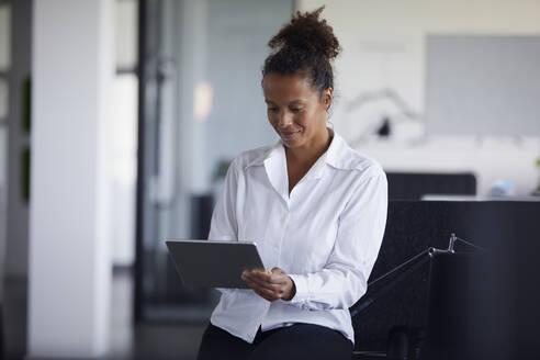 Portrait of smiling businesswoman using digital tablet in modern office - RBF07749