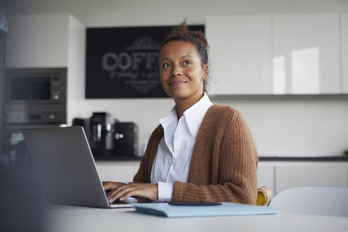 Portrait of smiling businesswoman working on laptop in kitchen - RBF07752