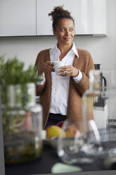 Portrait of smiling businesswoman standing in kitchen with cup of coffee looking at distance - RBF07755