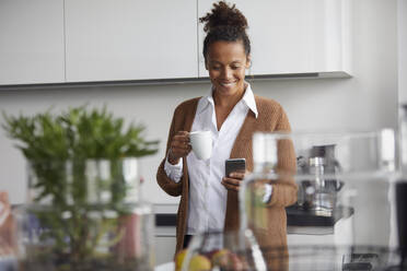 Portrait of smiling businesswoman standing in kitchen with cup of coffee looking at mobile phone - RBF07758
