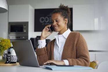 Smiling businesswoman on the phone sitting in kitchen working on laptop - RBF07761