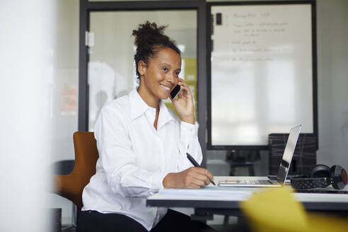 Portrait of smiling businesswoman on the phone sitting at desk in office - RBF07764