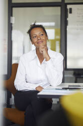 Portrait of smiling businesswoman sitting at desk in office - RBF07767