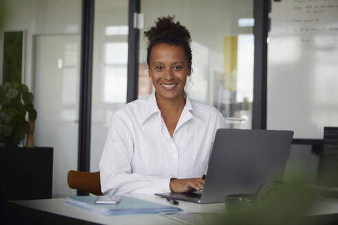 Portrait of smiling businesswoman working on laptop in office - RBF07770