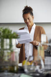Portrait of smiling businesswoman standing in kitchen looking at contract - RBF07773