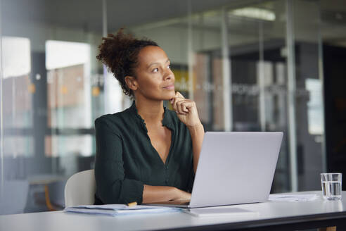 Portrait of pensive businesswoman sitting at desk with laptop looking at distance - RBF07776