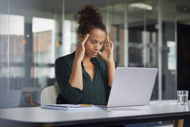 Portrait of pensive businesswoman at desk looking at laptop - RBF07779